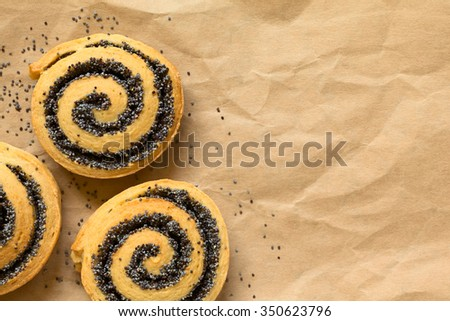 Homemade poppy seed rolls on paper, photographed overhead with natural light (Selective Focus, Focus on the top of the rolls) - stock photo