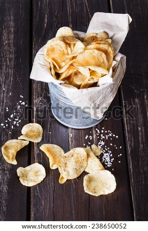 Homemade potato chips in a rustic metal bucket over dark wooden background. Selective focus - stock photo
