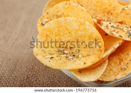 Homemade potato chips in glass bowl on table - stock photo