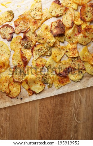 Homemade potato chips on wooden table - stock photo