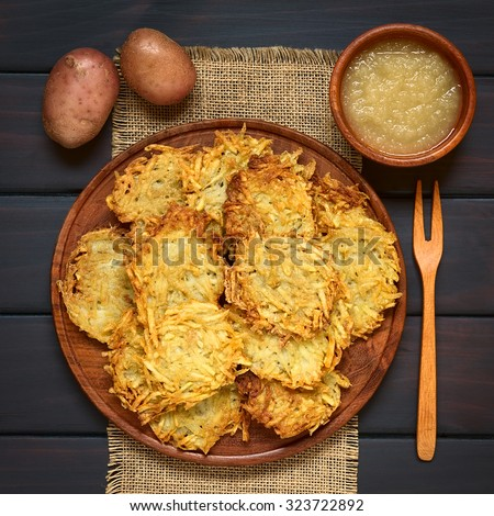 Homemade potato pancakes or fritters on wooden plate with apple sauce, a traditional dish in Germany, photographed overhead on dark wood with natural light - stock photo