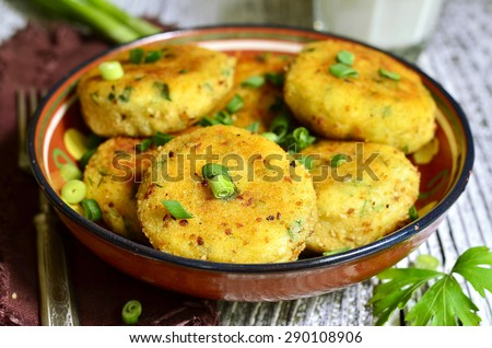 Homemade potato patties with herbs and green onion on rustic background. - stock photo