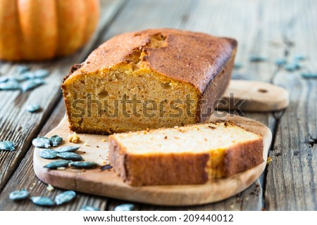 Homemade pound cake baked in a loaf pan on a wooden board - stock photo