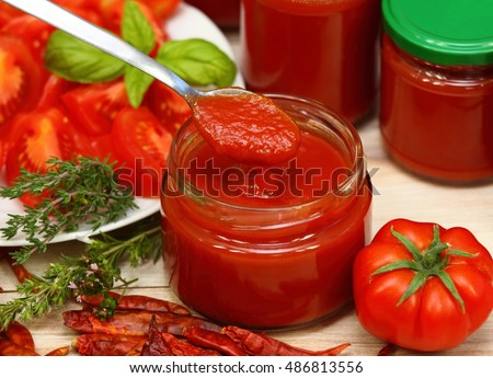 Homemade preserved  ketchup and jars of fresh ketchup at the background