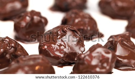 Homemade prunes in chocolate candies on white table background - stock photo