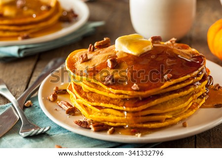 Homemade Pumpkin Pancakes with Butter Pecans and Maple Syrup - stock photo