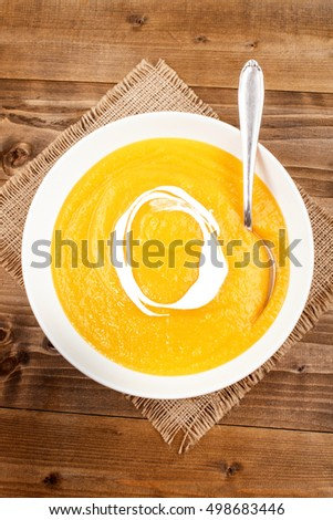 homemade pumpkin soup with sour cream in a deep plate on jute