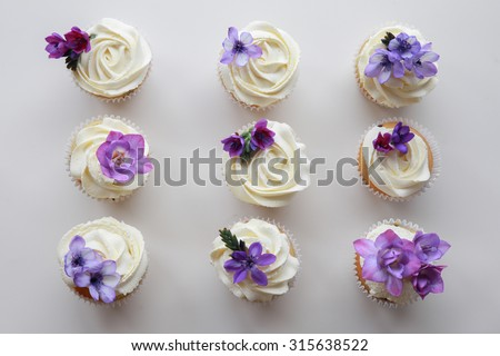 Homemade purple freesia flowers on vanilla cupcakes with whipped cream frosting - stock photo