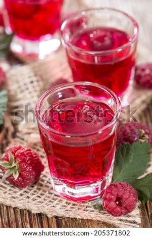 Homemade Raspberry Liqueur with fresh fruits on wooden background