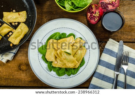 Homemade ravioli stuffed with spinach and ricotta, fresh pomegranate - stock photo