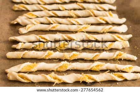 Homemade Raw Breadsticks before baking. Twisted strips of raw dough with cheese and sesame seeds freshly prepared for baking. - stock photo