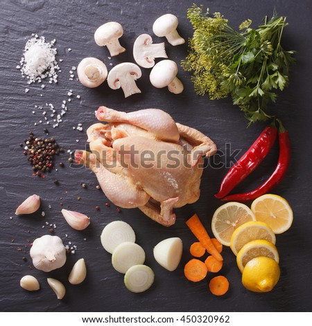 Homemade raw chicken with ingredients for cooking close up on a slate board. view from above - stock photo