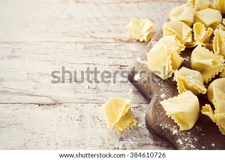 Homemade raw Italian saccottini filled with green pesto on wooden vintage cutting board. Retro style toned. With copy space. - stock photo