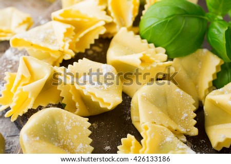 Homemade raw Italian saccottini filled with green pesto on wooden vintage cutting board with basil leaves. Selective focus. - stock photo