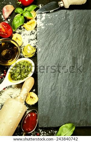 Homemade raw Italian tortellini and basil leaves and pesto on dark vintage background - stock photo
