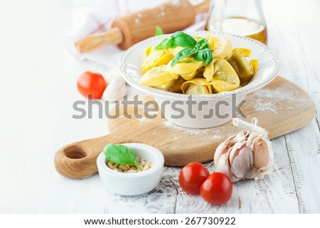 Homemade raw Italian tortellini and basil leaves on a white background, selective focus - stock photo