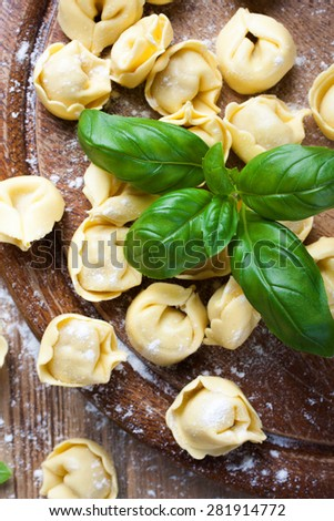 Homemade raw Italian tortelloni on wooden vintage cutting board with basil. Selective focus. Top view. - stock photo