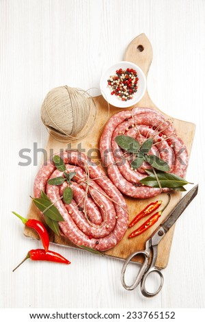 homemade raw sausage with herbs aromatic & fresh red pepper. ready for cooking. on wooden board - stock photo
