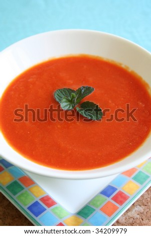 Homemade red pepper soup garnished with a sprig of black mint - lovely served hot or chilled for the summer. - stock photo