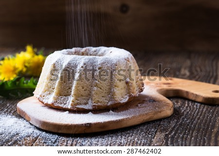 Homemade ring cake  with icing sugar on a rural wooden board on the background of spring dandelions - stock photo