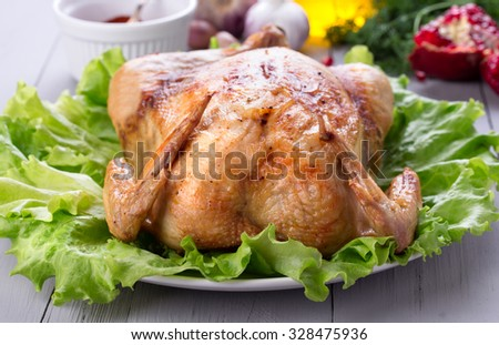 Homemade roasted chicken for festive dinner with pomegranate, red pepper and garlic. Thanksgiving or christmas day dish. - stock photo