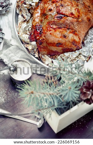 Homemade roasted pork for Christmas dinner, with seasoning and decorations - stock photo