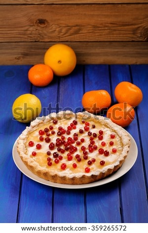 Homemade round lemon pie decorated with fresh cranberries and whole orange, lemon and clementines on deep blue table  - stock photo