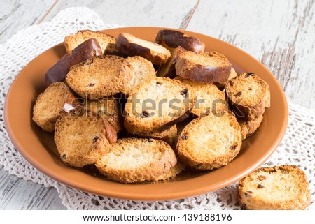 Homemade rusks on a brown ceramic plate on a napkin on a light wooden background.