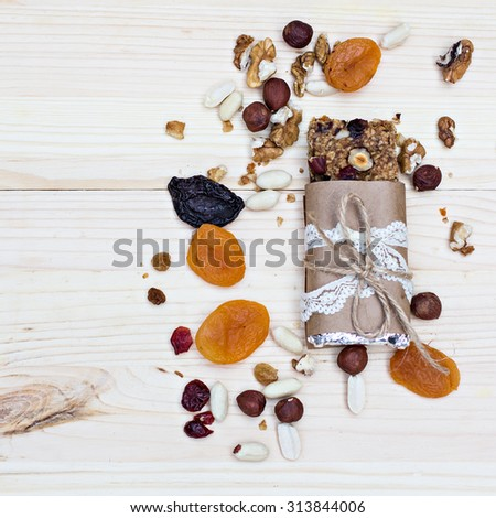 Homemade rustic granola bars with dried fruits and handmade packaged  on wooden background - stock photo