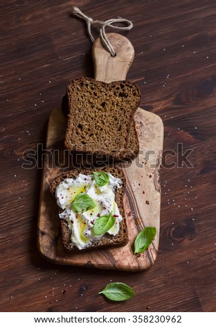 Homemade rye bread and lemon, basil, ricotta and honey bruschetta on a brown wooden table. Rustic style - stock photo