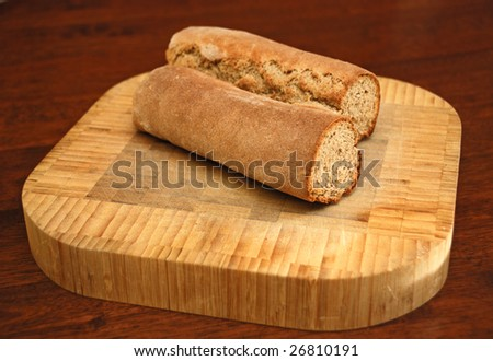 Homemade rye caraway bread cut in half on a wooden cutting board on a table. - stock photo