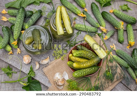 Homemade salted cucumbers in a glass jar on the background of fresh cucumbers, garlic and dill, top view - stock photo