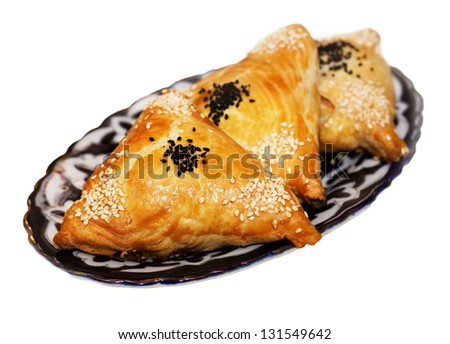 Homemade samosas on a plate isolated on white background - stock photo