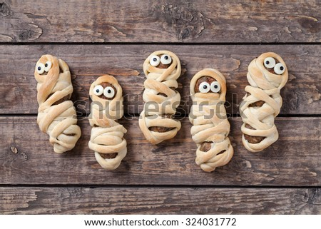 Homemade sausage meatball mummies wrapped in dough and baked for halloween celebration party. Vintage wooden background. Rustic style and natural light. - stock photo