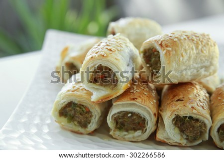 Homemade sausage rolls on white plate - stock photo