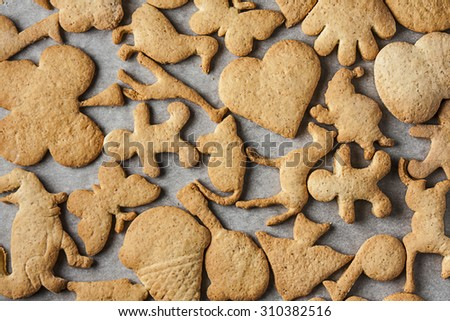Homemade shaped biscuits on oven paper - stock photo
