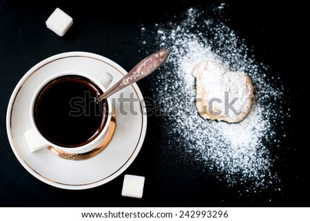 Homemade shortbread cookies, sprinkle with powdered sugar and a cup of coffee, spilling powdered sugar on a black background - stock photo