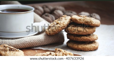 homemade shortbread cookies with nuts and a cup of strong black tea on the table - stock photo