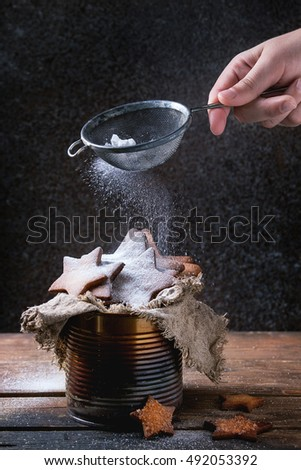 Homemade shortbread star shape sugar cookies different size in old tin can sackcloth rag with sieve sprinkling sugar powder from child hand on dark wooden background. Christmas treats.