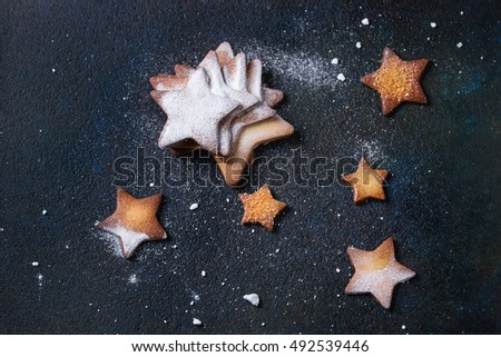 Homemade shortbread star shape sugar cookies different size with sugar powder on black textural surface. Christmas treats background. Overhead view