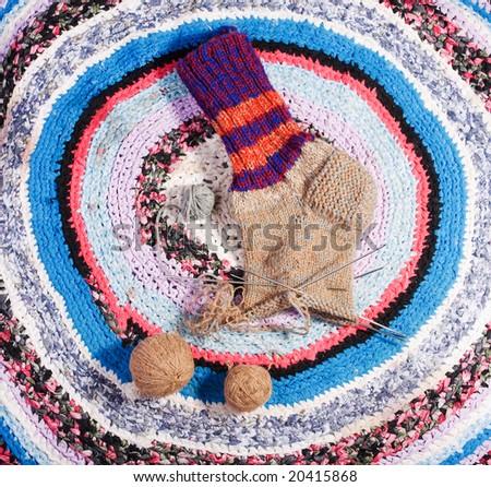 Homemade sock on a homemade carpet - stock photo
