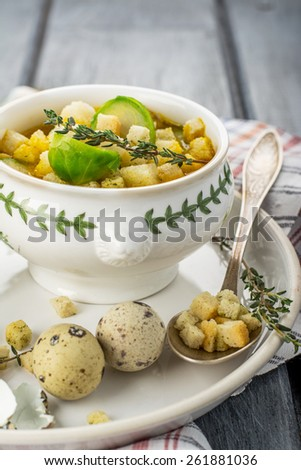 Homemade soup with brussels sprouts and croutons in white bowl decorated with a sprig of thyme. selective Focus - stock photo
