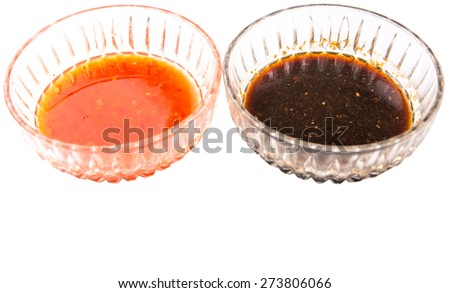 Homemade soy sauce and chili sauce in bowls over white background - stock photo