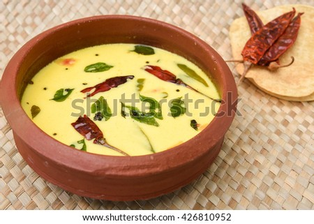 Homemade spiced butter milk or butter milk or moru / curd curry in clay pot made from cow milk with pappad / papar / pappadom in Kerala, India. Indian flavoured buttermilk. - stock photo