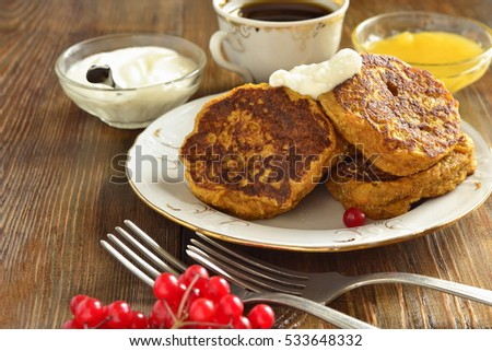 Homemade spicy pumpkin pancakes with honey and sour cream, fritters