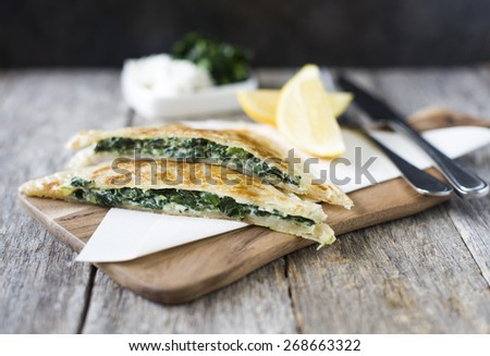 Homemade spinach and feta cheese pastry serving on wooden board - stock photo