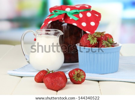 Homemade strawberry jam, on  napkin, on color wooden table, on bright background