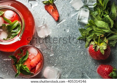 Homemade strawberry lemonade with mint and ice, served with fresh berries over metal tray surface, top view, copy space. Food frame and background
