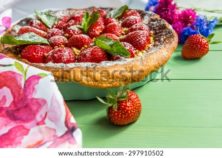 Homemade strawberry tart. Cornflowers are in background. Direct view
