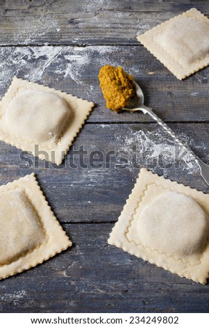 homemade stuffed with pumpkin ravioli big size on wooden table with flour and spoon - stock photo